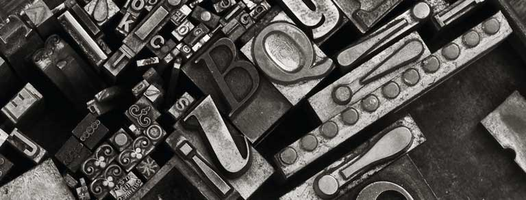 Masthead Graphic: A variety of metal type sorts for handset letterpress printing in a resorting tray.